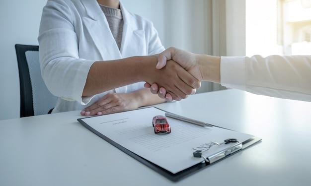 Handdruk van samenwerking tussen klant en verkoper na ondertekening van de contractovereenkomst, succesvolle aankoop van autoleningen of autoverhuur.