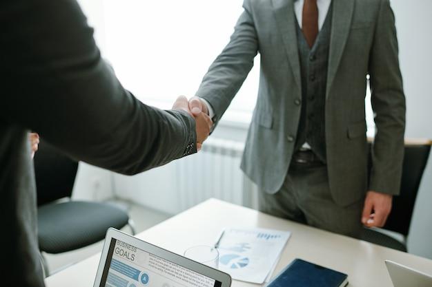 Handdruk van twee elegante zakenpartners of hr-manager en sollicitant op bureau met documenten en laptops na ondertekening contract