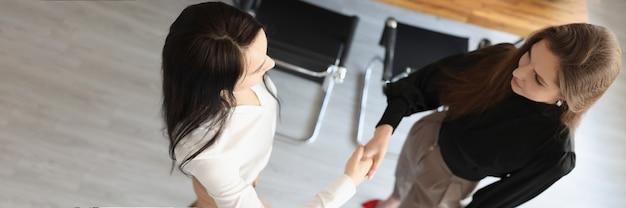 Handdruk van twee zakenvrouwen in het bovenaanzicht van het kantoor