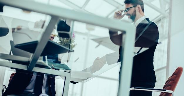 Handdruk van werknemers op de werkplek in een modern kantoor. de foto heeft een lege ruimte voor uw tekst