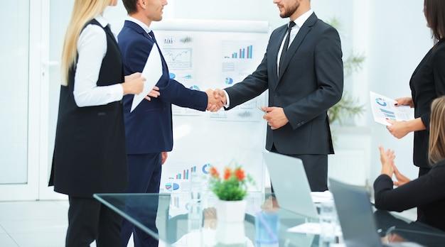 Handdruk van zakenpartners van de financiële grafieken van het nieuwe project