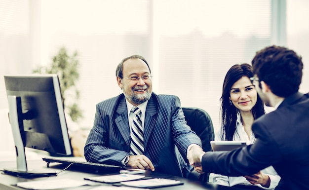 Handdruk zakenpartners na bespreking van de financiële voorwaarden van het contract. de foto heeft een lege ruimte voor uw tekst