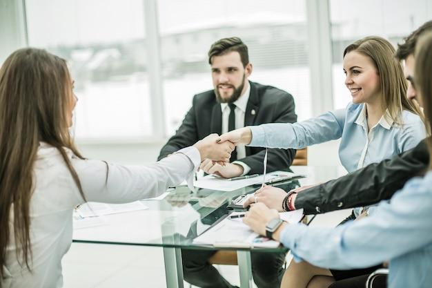 Handdruk zakenpartners na bespreking van de voorwaarden van een nieuw contract op de werkplek in een modern kantoor