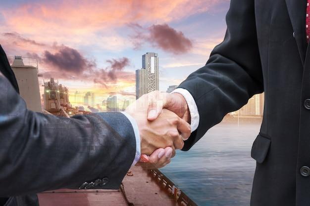 Handdrukovereenkomst van zakenman met partnerschap over de invoer van vrachtschepen naar de achtergrond van de stad