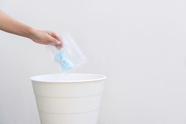 Handdruppel gebruikt medisch masker in de prullenbak