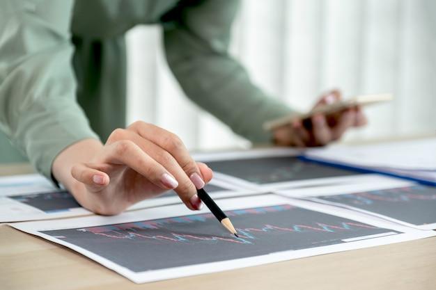 Handelaar vrouw houdt potlood vast en analyseert aandelengrafiekrapport, stelt doelen voor online forex tradin