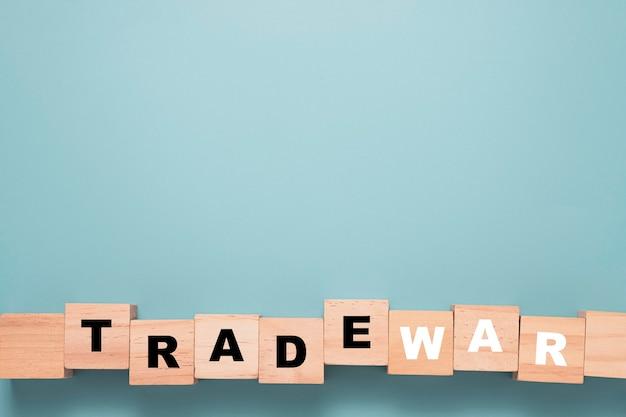 Handelsoorlog formulering afdrukscherm op houten blok kubus met blauwe achtergrond.