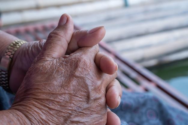 Handen aziatische oudere vrouw grijpt haar hand op schoot
