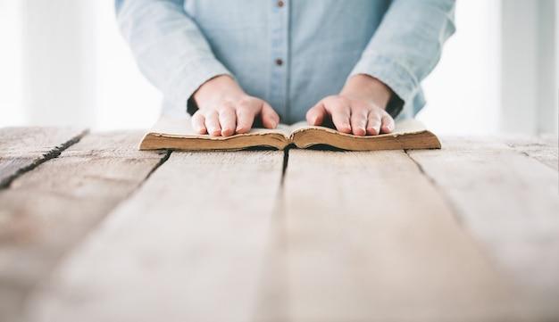Handen bidden met een bijbel over houten tafel