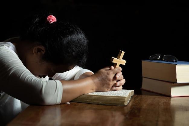 Handen bidden tot god terwijl ze het kruissymbool vasthouden.