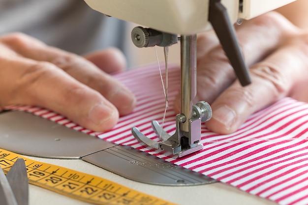 Handen bij de naaimachine die wat stof vasthouden