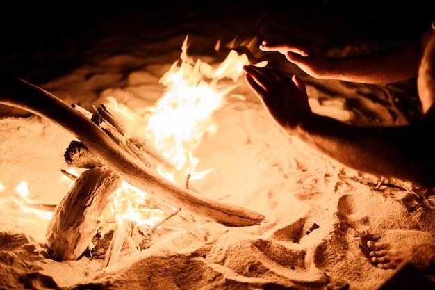 Handen bij het vuur op het strand