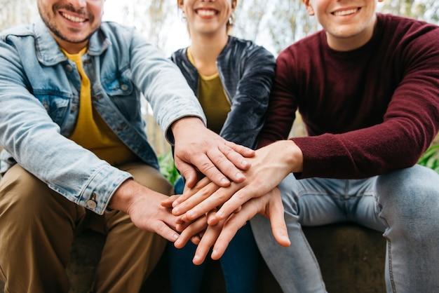 Handen bovenop elkaar van glimlachende vrienden op achtergrond