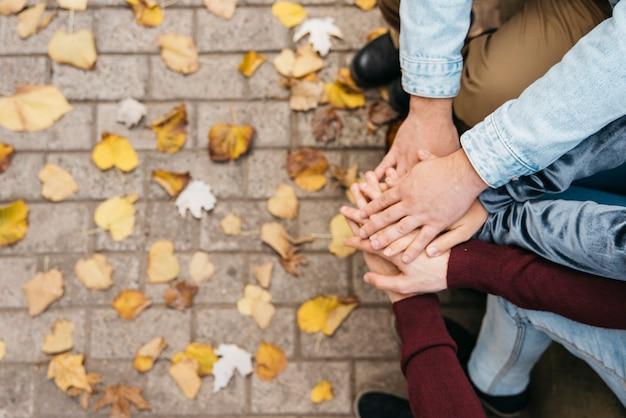 Handen bovenop elkaar van vrienden