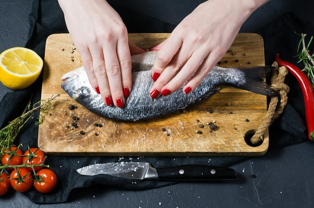 Handen chef-kok gezouten dorado vis op een houten snijplank
