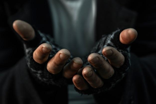 Handen close-up arme oude man of bedelaar smeekt je om hulp bij vuile sloppenwijk