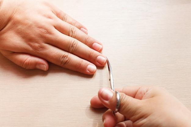 Handen close-up, een meisje doet een manicure aan zichzelf, nagelschaartje.
