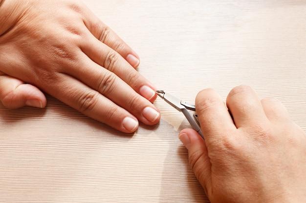 Handen close-up, een meisje doet een manicure voor zichzelf, nagelknipper.