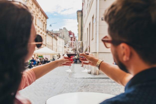 Handen close-up van paar roosterende glazen wijn
