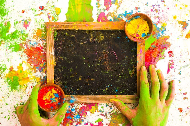 Handen dichtbij kader met kleuren in kommen tussen heldere droge kleuren