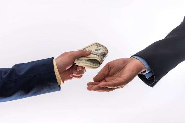 Handen die 100 geïsoleerde dollarbiils geven