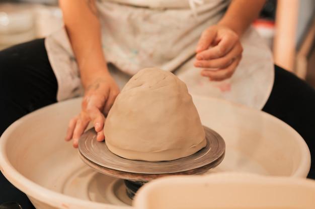Handen die aan aardewerkwiel werken