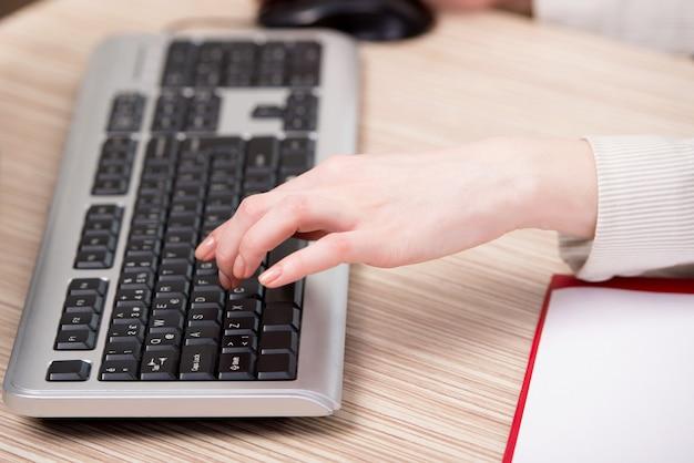 Handen die aan het toetsenbord op het kantoor werken