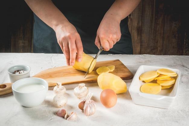 Handen die aardappel snijden die door ingrediënten wordt omringd