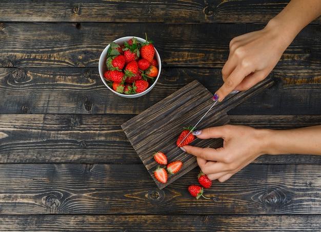 Handen die aardbeien met mes op houten raad snijden