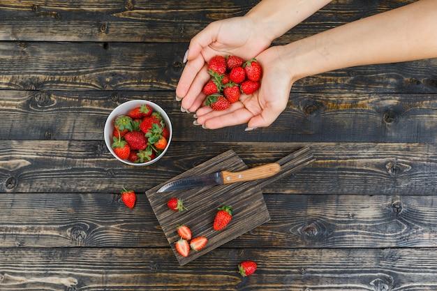 Handen die aardbeien vangen in een houten bord