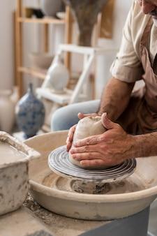 Handen die aardewerk doen close-up