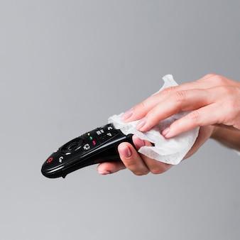 Handen die afstandsbediening desinfecteren