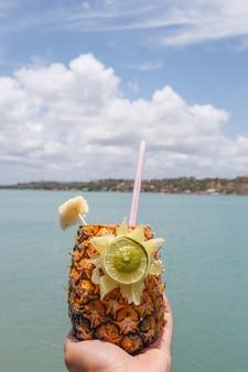 Handen die ananasdrank met strandachtergrond houden.