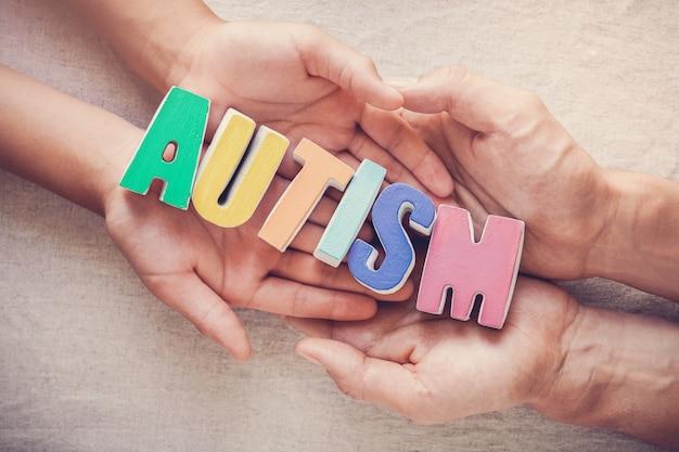 Handen die autismewoord, geestelijke gezondheidsconcept, de voorlichtingsdag van het wereldautisme houden