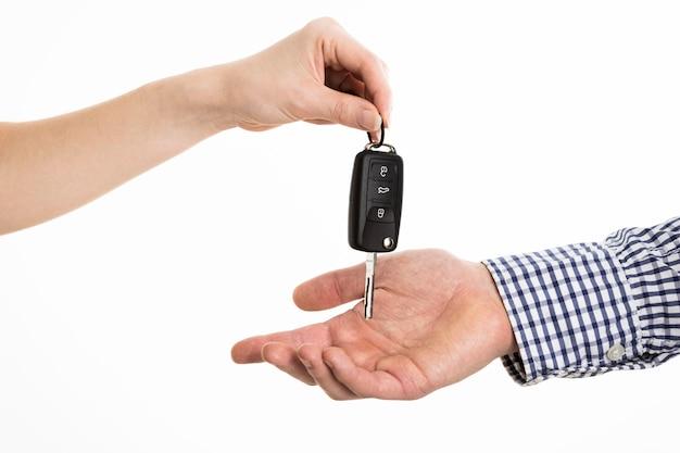 Handen die autosleutels uitwisselen