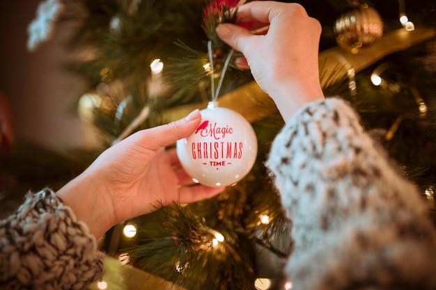 Handen die bal op kerstboom zetten