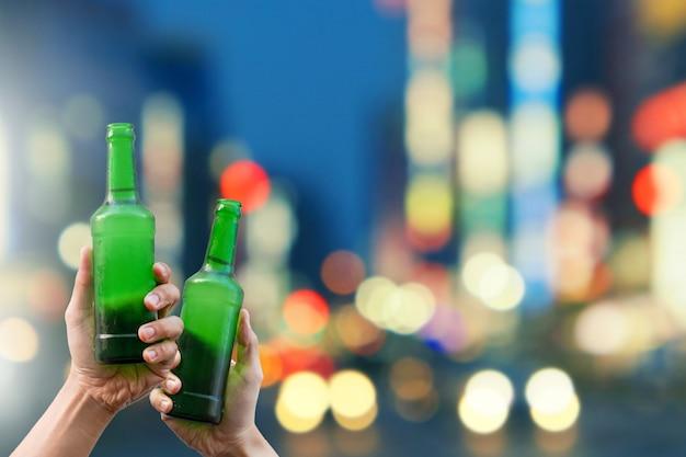 Handen die bierflessen houden en gelukkige samen genietend van oogsttijd aan clinking glazen bij openluchtpartij op het mooie licht van de bokehnacht
