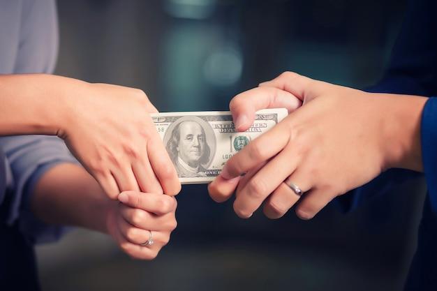 Handen die bij stapel bankbiljetten trekken