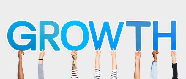 Handen die blauwe letters omhoog houden die het woord groei vormen