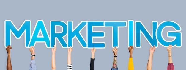 Handen die blauwe letters omhoog houden die het woord marketing vormen