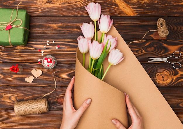 Handen die bloemen op houten lijst verpakken