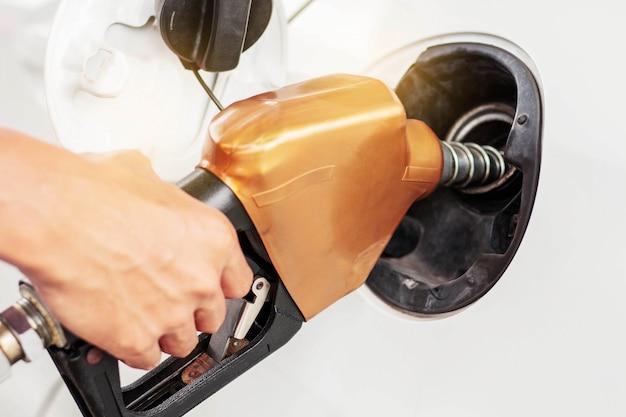Handen die brandstof voor auto's aflossen.