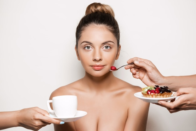 Handen die cake en dranken aanbieden aan jonge mooie vrouw