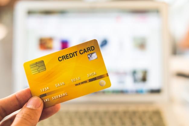 Handen die creditcard houden en laptop met behulp van