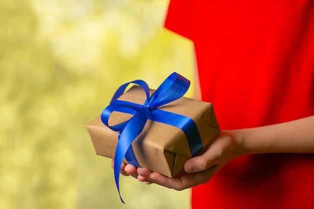 Handen die de doos van de ambachtgift met blauw lint houden