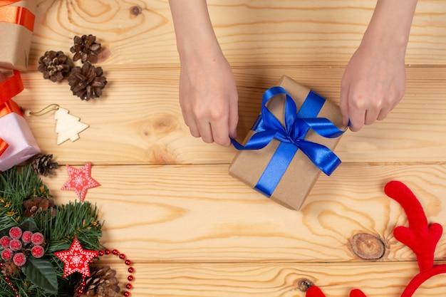 Handen die de gift van kerstmis inpakken op houten