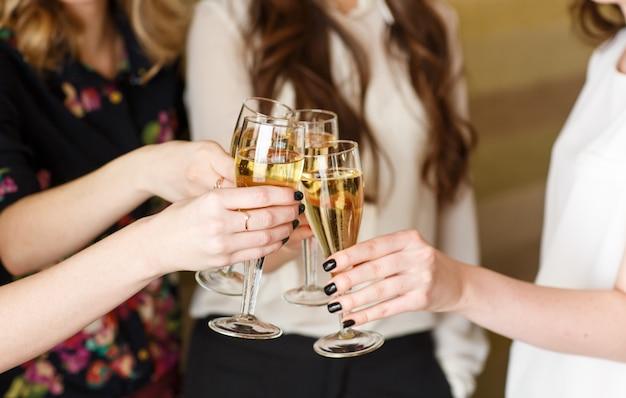 Handen die de glazen champagne houden die een toost maken