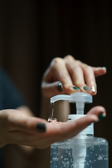 Handen die de handpomp gebruiken. helder ontsmettingsmiddel in pompfles, voor het doden van ziektekiemen, bacteriën en virussen.