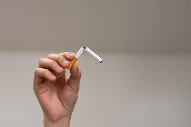 Handen die de sigaret vasthouden en breken om te stoppen met roken stop met roken voor gezondheidsconcept
