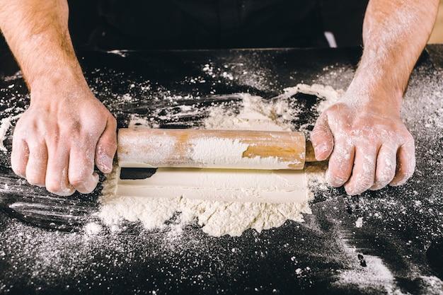 Handen die deeg met deegrol bakken